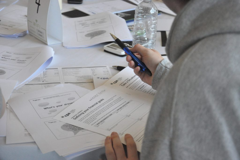 Student filling out worksheet at Foundations of Finance event