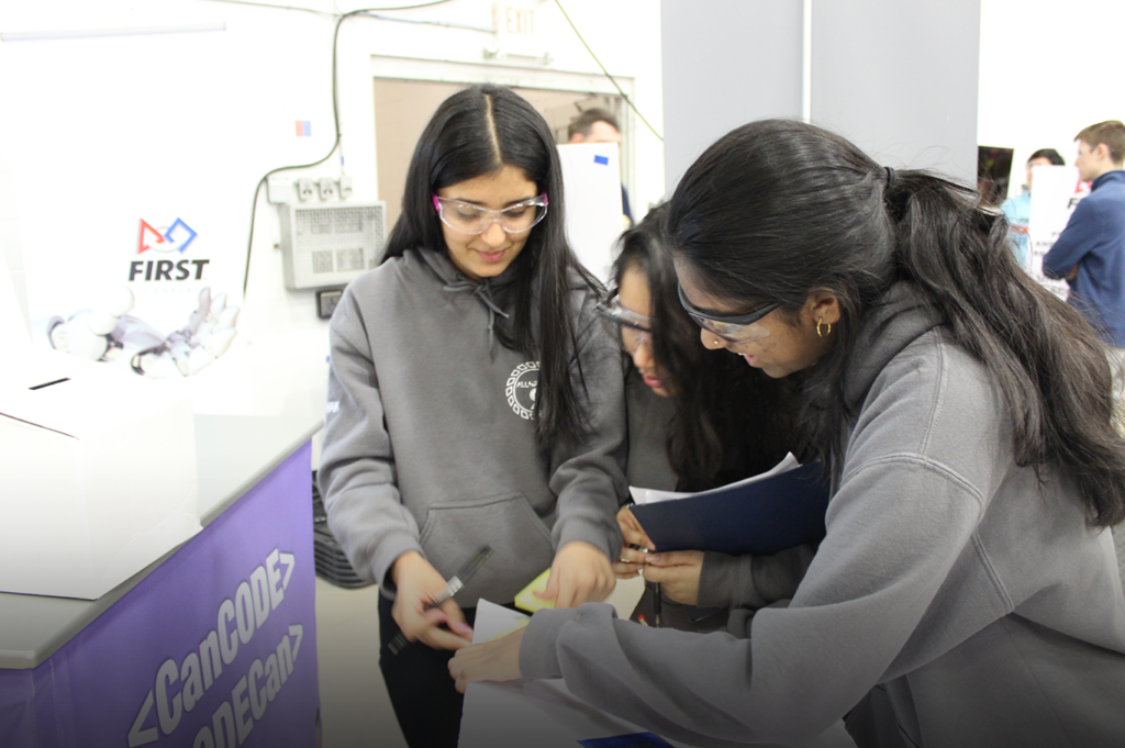 Three females writing on a paper for FIRST Robotics